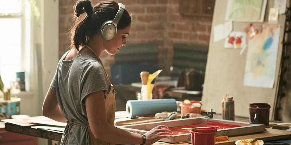 Девушка в наушниках с активным шумоподавлением Bose QuietComfort 35