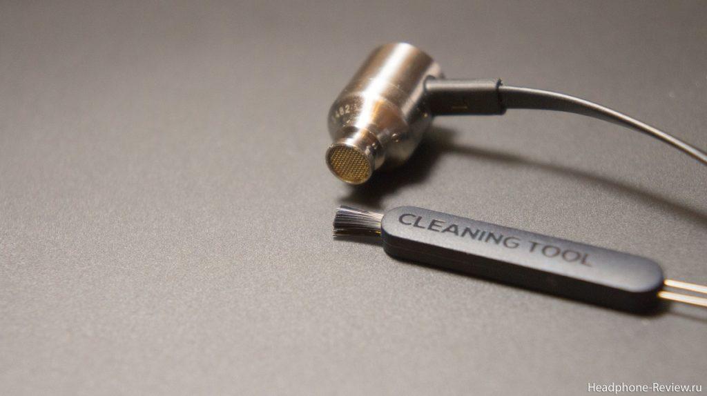 Чистка защитной сетки наушника чистящей щёткой от ушной серы